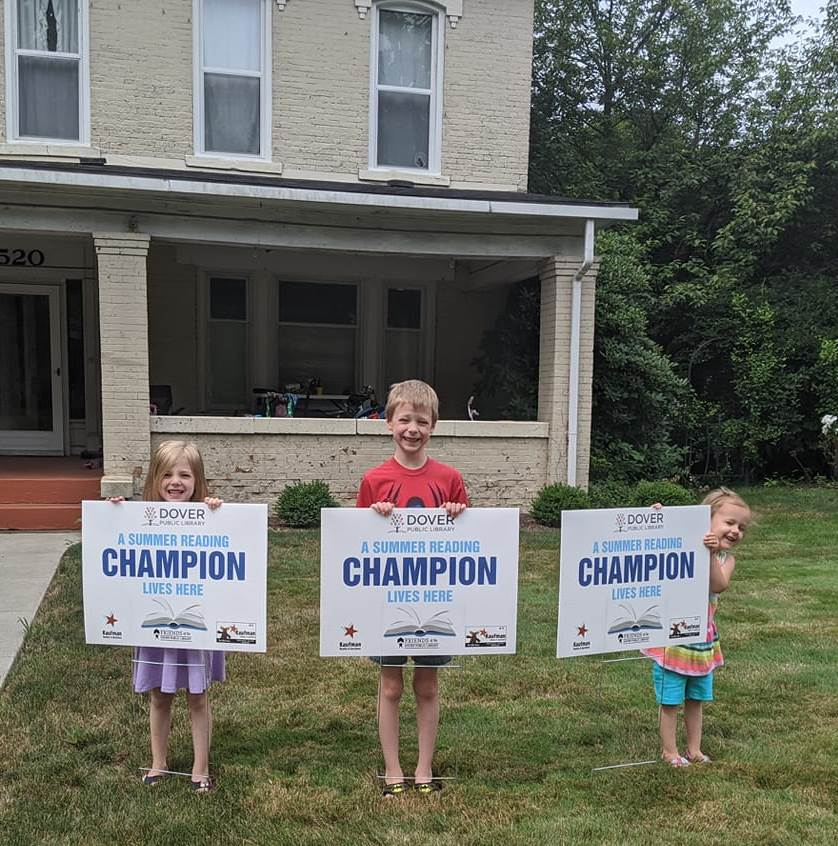 Kids holding reading champion signs
