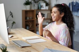 girl saying hello to remote teacher photo