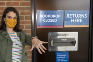 Woman with diamond ring in front of book drop photo