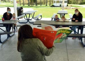 photo of storytime at picnic tables